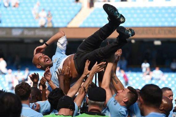 Pep Guardiola es levantado por sus jugadores del Manchester City.